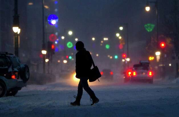 A woman crosses Congress Street during a snow storm, Friday, Feb. 8, 2013, in Portland, Maine. Snow began falling across the Northeast on Friday, ushering in what was predicted to be a huge, possibly historic blizzard and sending residents scurrying to stock up on food and gas up their cars. The storm could dump 1 to 3 feet of snow from New York City to Boston and beyond. Photo: Robert F. Bukaty, Associated Press / AP