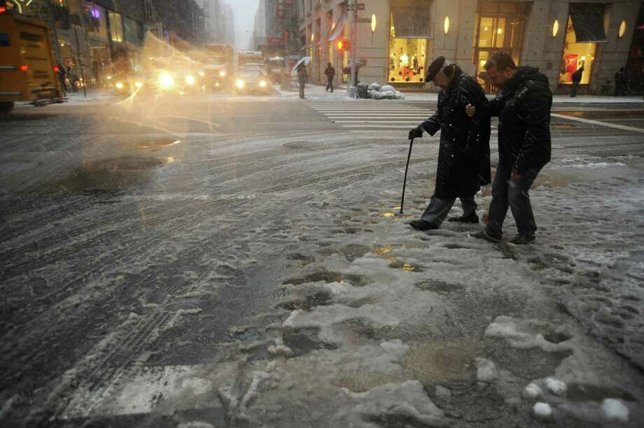 "New York City residents cross a street covered in slush on February 8, 2013 during a storm affecting the northeast US. The storm was forecast to bring the heaviest snow to the densely-populated northeast corridor so far this winter, threatening power and transport links for tens of millions of people and the major cities of Boston and New York. New York and other regional airports saw more than 4,500 cancellations ahead of what the National Weather Service called ""a major winter storm with blizzard conditions"" along most of the region's coastline. Photo: MEHDI TAAMALLAH, AFP/Getty Images / Taamallah"