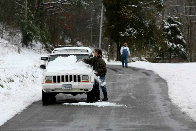 Belinda Sink, of Roanoke County, stops to sweep off her windshield with her hand after her blades didn't move as she drove, Friday, Feb. 8, 2013.  Neighbor, Darrell Ward walked down the road to check to make sure she was okay. Photo: Stephanie Klein-Davis, Associated Press / The Roanoke Times