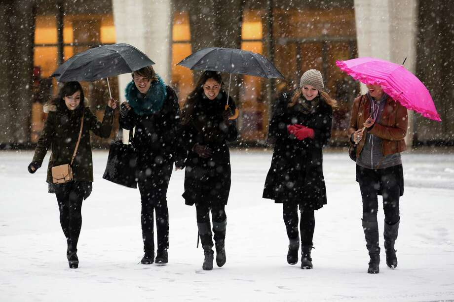 Pedestrians walk through the snow at Lincoln Center during Fashion Week, Friday, Feb. 8, 2013, in New York. Snow began falling across the Northeast on Friday, ushering in what was predicted to be a huge, possibly historic blizzard and sending residents scurrying to stock up on food and gas up their cars. Photo: John Minchillo, Associated Press / FR170537 AP