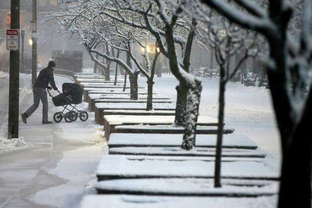 A man wheels a stroller through snow in the Boston Commons early Friday evening, Feb. 8, 2013 in Boston. Snow began falling across the Northeast on Friday, ushering in what was predicted to be a huge, possibly historic blizzard and sending residents scurrying to stock up on food and gas up their cars. The storm could dump 1 to 3 feet of snow from New York City to Boston and beyond. Photo: Gene J. Puskar, Associated Press / AP