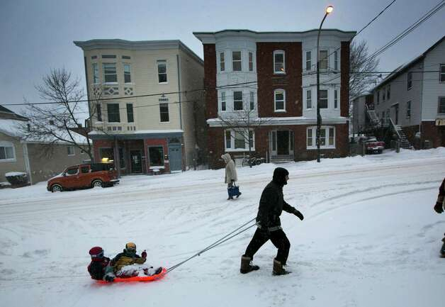 Guy McChesney pulls Lucas McChesney and Nico Doyle on a sled up Munjoy Hill during a snow storm, Friday, Feb. 8, 2013, in Portland, Maine. Snow began falling across the Northeast on Friday, ushering in what was predicted to be a huge, possibly historic blizzard and sending residents scurrying to stock up on food and gas up their cars. The storm could dump 1 to 3 feet of snow from New York City to Boston and beyond. Photo: Robert F. Bukaty, Associated Press / AP