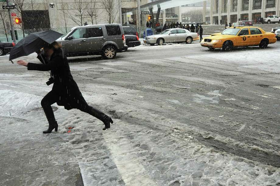 "A woman crosses a street covered in slush in New York on February 8, 2013 during a storm affecting the northeast US. The storm was forecast to bring the heaviest snow to the densely-populated northeast corridor so far this winter, threatening power and transport links for tens of millions of people and the major cities of Boston and New York. New York and other regional airports saw more than 4,500 cancellations ahead of what the National Weather Service called ""a major winter storm with blizzard conditions"" along most of the region's coastline. Photo: MEHDI TAAMALLAH, AFP/Getty Images / Taamallah"