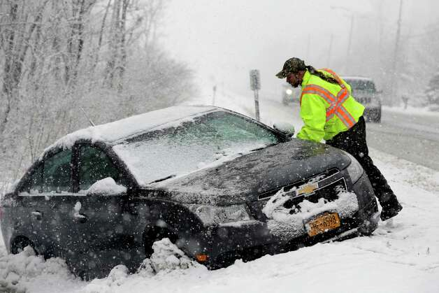Tow truck operator Shawn Juhre looks over a car before towing it out of a ditch during a winter snow storm in Buffalo, N.Y., Friday, Feb. 8, 2013. Photo: David Duprey, Associated Press / AP