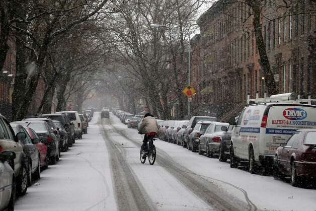 A man rides a bike down a snowy street on February 8, 2013 in New York City. New York City and much of the Northeast is expected to get a foot or more of snow through Saturday afternoon with possible record-setting blizzard conditions expected in Boston, Massachusetts. Heavy snow warnings are in effect from New Jersey through southern Maine. Photo: Michael Heiman, Getty Images / 2013 Getty Images