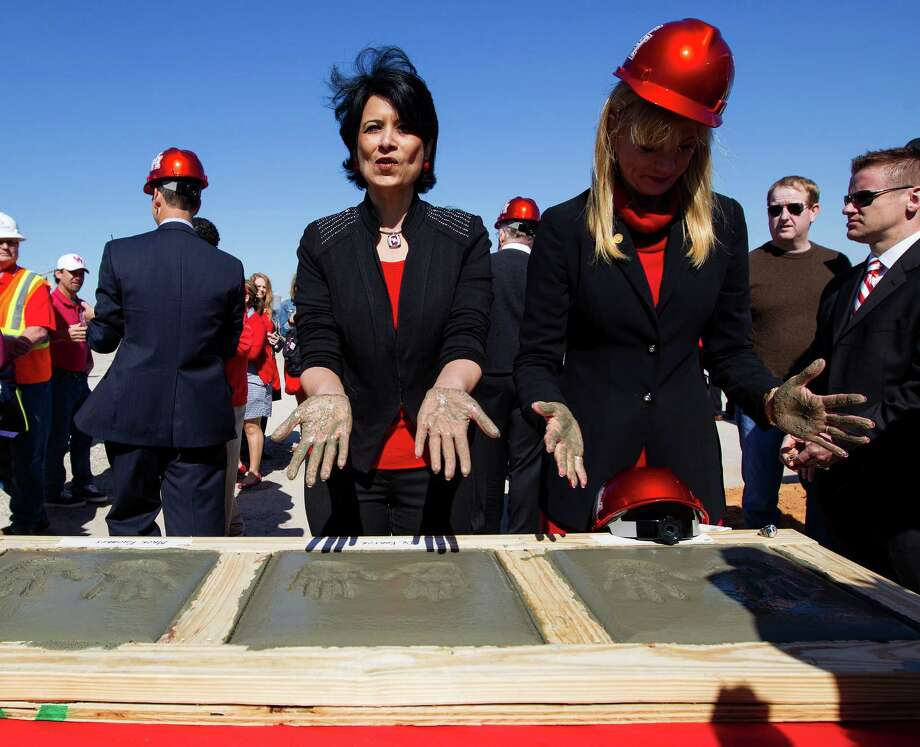 University of Houston president Renu Khator, left, and Nelda Luce Blair, right, Chairman of the UH System Board of Regents, lift their hands out of the cement blocks during the groundbreaking ceremony for the new University of Houston football stadium, Friday, Feb. 8, 2013, in Houston.  The Houston football stadium will contain a minimum of 40,000 seats and will be completed by August 2014. ( Karen Warren / Houston Chronicle ) Photo: Karen Warren, Staff / © 2013 Houston Chronicle