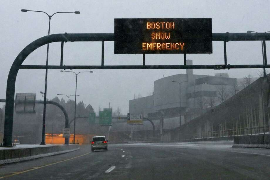 A vehicle moves down a nearly empty highway as a sign warns of a snow emergency at the entrance to the Ted Williams Tunnel in Boston. Photo: Gene J. Puskar / Associated Press