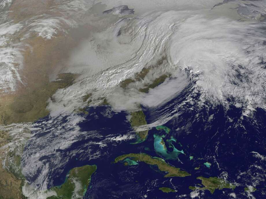 This image released by NASA from NOAA's GOES-13 satellite captured at 9:01 a.m. on Friday, Feb. 8, 2013 shows a massive winter storm coming together as two low pressure systems merge over the northeast U.S. Snow began falling across the Northeast on Friday, ushering in what was predicted to be a huge, possibly historic blizzard and sending residents scurrying to stock up on food and gas up their cars. (AP Photo/NASA) Photo: Uncredited