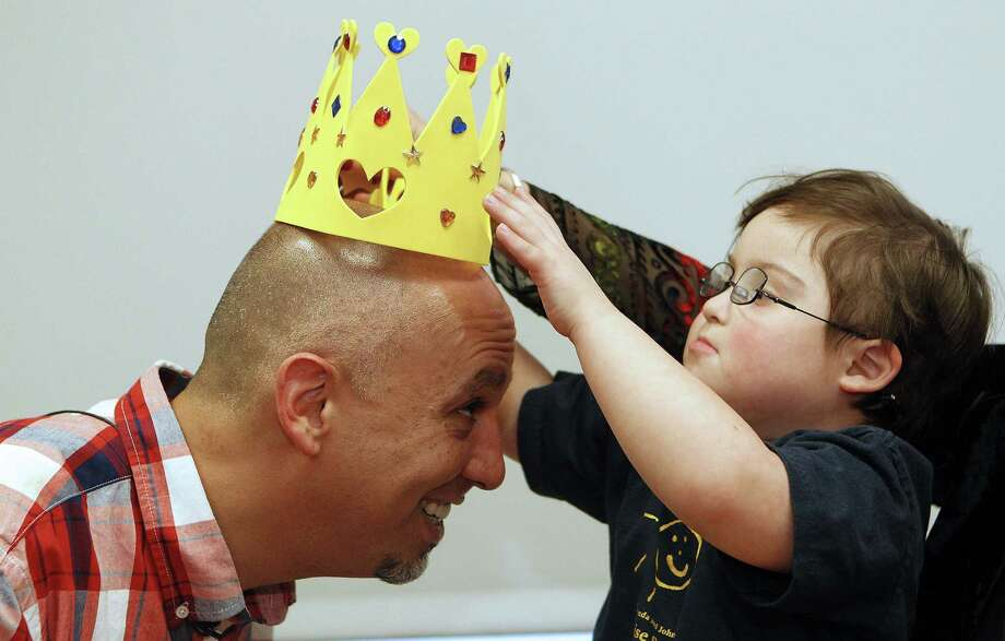 Michael Garcia has a crown placed on his head by his new friend, 5-year-old Milo Castillo, after students and teachers from the Rise School of Houston honored the waiter. Photo: Johnny Hanson / Houston Chronicle