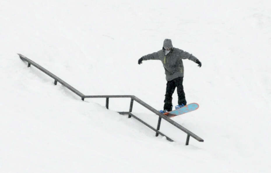 A snowboarder grinds a rail as he takes advantage of the snowy weather at West Mountain ski area on