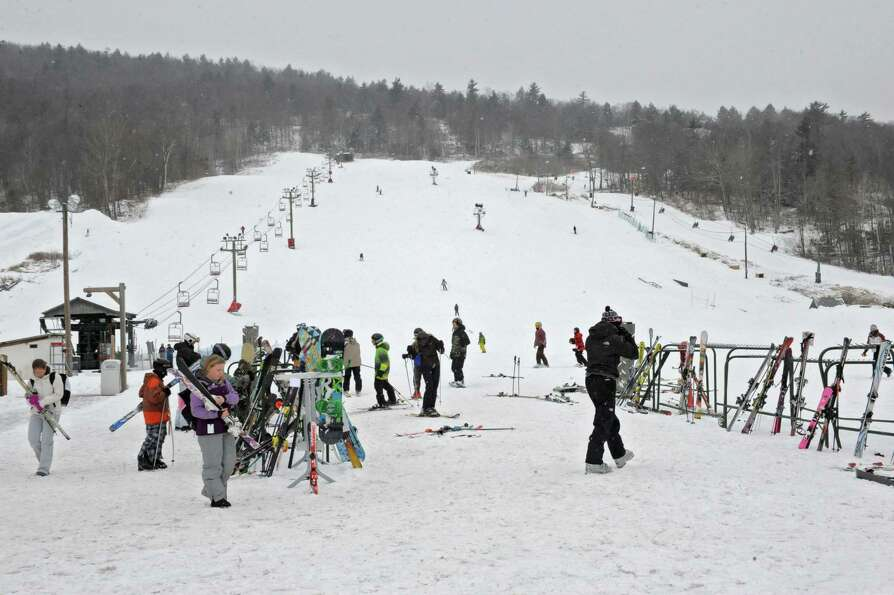 Snowboarders and skiers take advantage of the snowy weather at West Mountain ski area on Friday Feb.