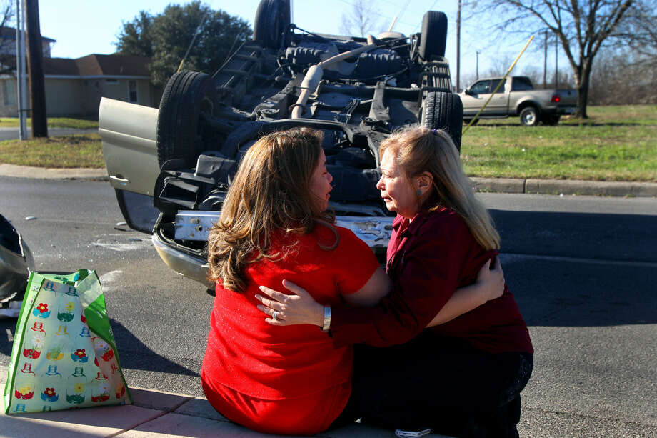 Cristella Ireland (left) embraces her mother, Trini Macias, after Ireland's minivan flipped as she was heading north on New Guilbeau Road near Loop 1604 on Friday morning. She said she lost control after striking a curb and was treated at the scene for an arm injury. No other vehicles were involved. Photo: John Davenport / San Antonio Express-News