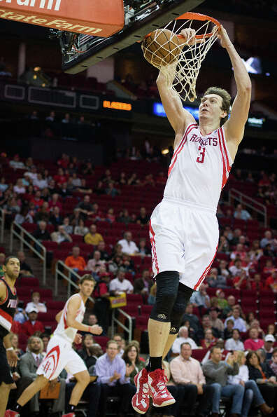 Rockets center Omer Asik (3) goes up for a dunk.