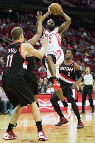 Rockets shooting guard James Harden (13) drives to the basket between Meyers Leonard (11) and Wesley Matthews. Photo: Smiley N. Pool, Houston Chronicle / © 2013  Houston Chronicle