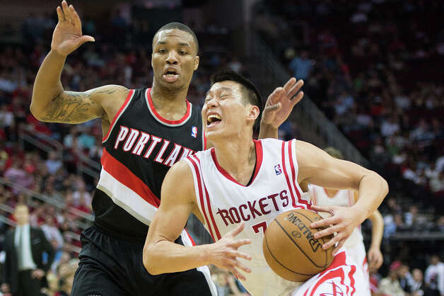 Rockets point guard Jeremy Lin (7) drives to the basket past Trail Blazers point guard Damian Lillard. Photo: Smiley N. Pool, Houston Chronicle / © 2013  Houston Chronicle