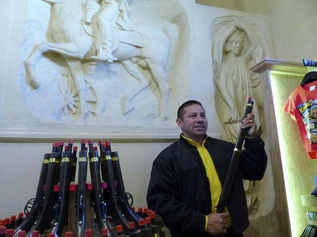 "Antonio Resendiz tries out a toy weapon at the Alamo Gift Shop on the day the ""re-imagined' store reopened. Photo: Photos By Billy Calzada / San Antonio Express-News"