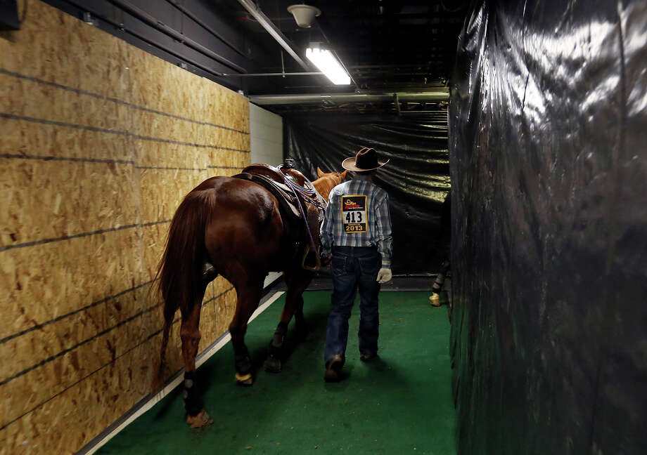 Tyler Wade Taylor, of Terrell, Texas,  walks his horse through the AT&T Center for the team roping event during the San Antonio Stock Show & Rodeo Friday Feb. 8, 2013 at the AT&T Center. Photo: Edward A. Ornelas, San Antonio Express-News / © 2013 San Antonio Express-News