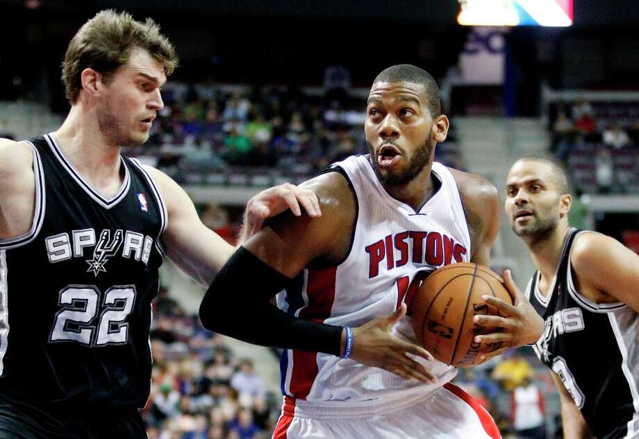 Detroit Pistons center Greg Monroe (10) drives to the basket against San Antonio Spurs center Tiago Splitter (22) in the second half of an NBA basketball game Friday, Feb. 8, 2013, in Auburn Hills, Mich. Monroe led the Pistons with 26 points and pulled in 16 rebounds in a 119-109 win. (AP Photo/Duane Burleson) Photo: Duane Burleson, Associated Press / FR38952 AP