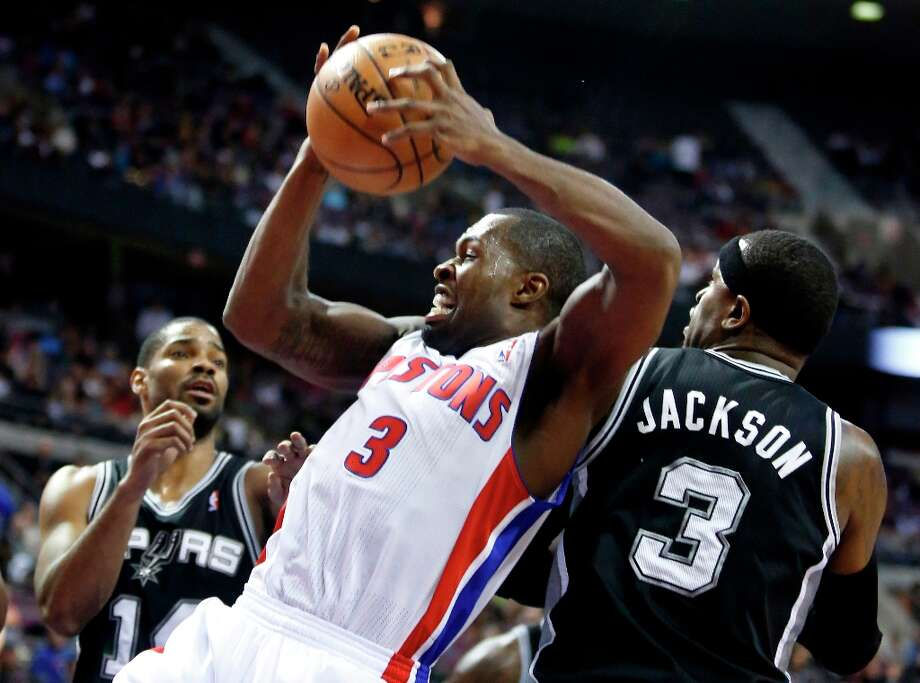 Detroit Pistons guard Rodney Stuckey (3) grabs a rebound in front of San Antonio Spur guard Gary Neal, left, and forward Stephen Jackson (3) in the second half of an NBA basketball game Friday, Feb. 8, 2013, in Auburn Hills, Mich. The Pistons defeated the Spurs 119-109. (AP Photo/Duane Burleson) Photo: Duane Burleson, Associated Press / FR38952 AP