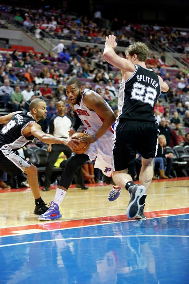 Detroit Pistons center Greg Monroe (10) drives to the basket between San Antonio Spur guard Tony Parker (9) and center Tiago Splitter (22) in the second half of an NBA basketball game Friday, Feb. 8, 2013, in Auburn Hills, Mich. (AP Photo/Duane Burleson) Photo: Duane Burleson, Associated Press / FR38952 AP