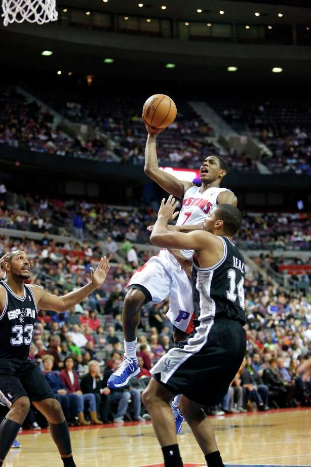 Detroit Pistons guard Brandon Knight (7) takes a shot against San Antonio Spurs center Boris Diaw (33) and guard Gary Neal (14) in the second half of an NBA basketball game Friday, Feb. 8, 2013, in Auburn Hills, Mich. (AP Photo/Duane Burleson) Photo: Duane Burleson, Associated Press / FR38952 AP