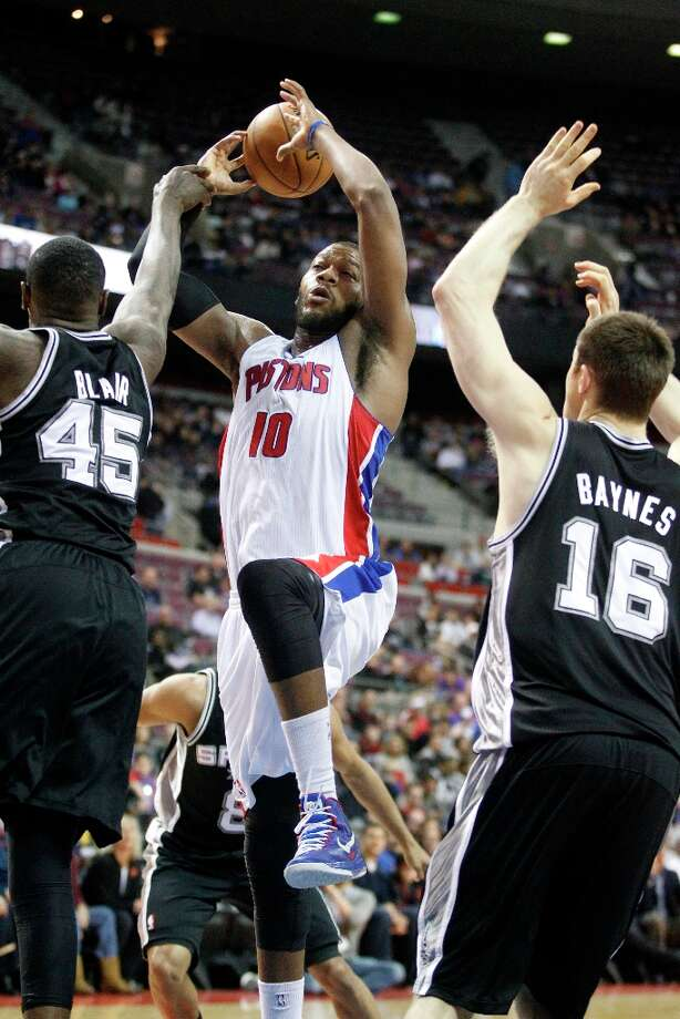 Detroit Pistons center Greg Monroe (10) goes to the basket between San Antonio Spurs center DeJuan Blair (45) and forward Aron Baynes (16) in the second half of an NBA basketball game Friday, Feb. 8, 2013, in Auburn Hills, Mich. (AP Photo/Duane Burleson) Photo: Duane Burleson, Associated Press / FR38952 AP