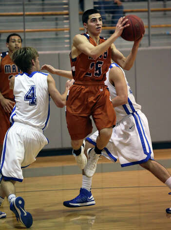 Madison's Troy Guajardo slips between defenders to take a shot as MacArthur plays Madison at the Lee High School gym  on February 8, 2013. Photo: Tom Reel, Express-News / ©2012 San Antono Express-News