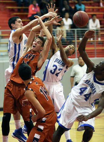 Brahma center Nick Garcia shoves the ball out of a heap to start a fastbreak as MacArthur plays Madison at the Lee High School gym  on February 8, 2013. Photo: Tom Reel, Express-News / ©2012 San Antono Express-News