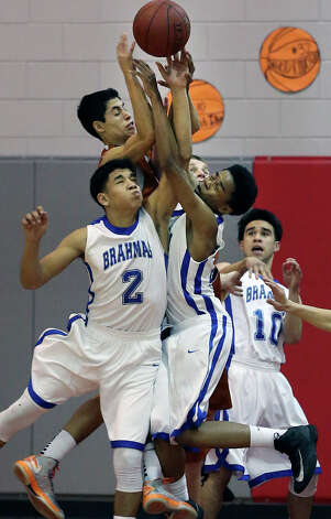 The Brahmas converge against Madison's Anthony Morales for a loose ball in the second half as MacArthur plays Madison at the Lee High School gym  on February 8, 2013. Photo: Tom Reel, Express-News / ©2012 San Antono Express-News