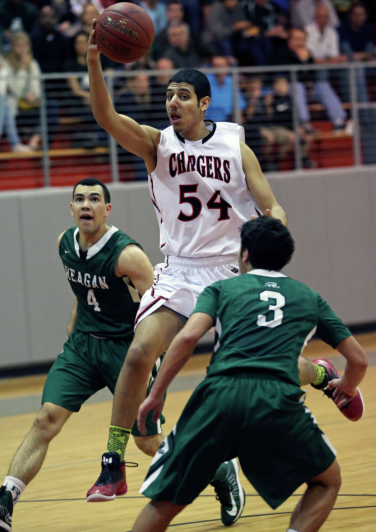 Charger center Abdulla Al-Bader throws a no look pass on a fast break to score as Reagan plays Churchill at the Lee High School gym on February 8, 2013.