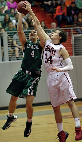 Taylor Sutlive  reaches over to get the block on Reagan guard Michael Williams as Reagan plays Churchill at the Lee High School gym  on February 8, 2013. Photo: Tom Reel, Express-News / ©2012 San Antono Express-News