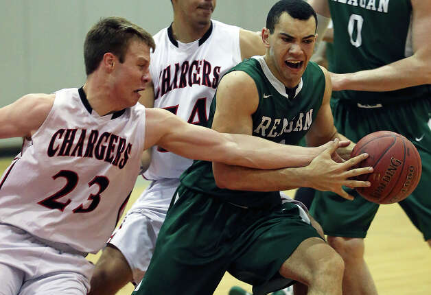 Charger guard Ben Mammel takes a slap at the ball through the hands of Reagan guard Michael Williams as Reagan plays Churchill at the Lee High School gym  on February 8, 2013. Photo: Tom Reel, Express-News / ©2012 San Antono Express-News