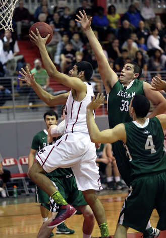 Charger big man Abdulla Al-Bader rolls in for a layup after beating Jordan Alvarado on the floor as Reagan plays Churchill at the Lee High School gym  on February 8, 2013. Photo: Tom Reel, Express-News / ©2012 San Antono Express-News