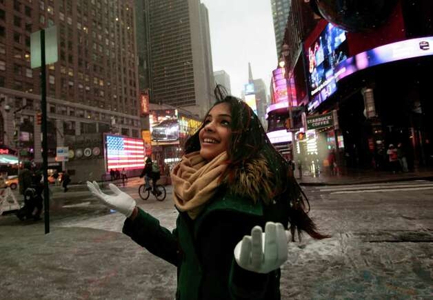 Ruth TTiburcio, of the Dominican Republic, stops to marvel at the snow in Times Square in New York City on Friday, February 8, 2013. A major blizzard is expected to hit the Northeast on Friday, including New York. (Carolyn Cole/Los Angeles Times/MCT) Photo: Carolyn Cole, McClatchy-Tribune News Service / Los Angeles Times