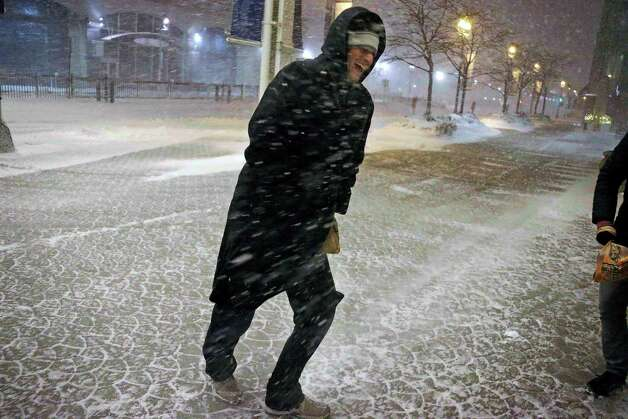 A guest at the Seaport Hotel crosses the street against the wind and snow Friday, Feb. 8, 2013 in Boston. Snow began falling across the Northeast on Friday, ushering in what was predicted to be a huge, possibly historic blizzard and sending residents scurrying to stock up on food and gas up their cars. The storm could dump 1 to 3 feet of snow from New York City to Boston and beyond. (AP Photo/Gene J. Puskar) Photo: Gene J. Puskar, Associated Press / AP