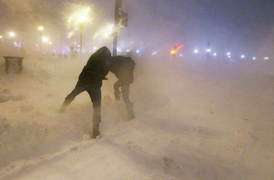 People shield themselves from the blowing snow as a blizzard arrives in the Back Bay neighborhood on