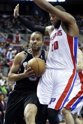 Guard Tony Parker (left), driving to the basket against Pistons center Greg Monroe, had 31 points and eight assists, but the Spurs' NBA-best 11-game winning streak still came to an end. Photo: Duane Burleson / Associated Press
