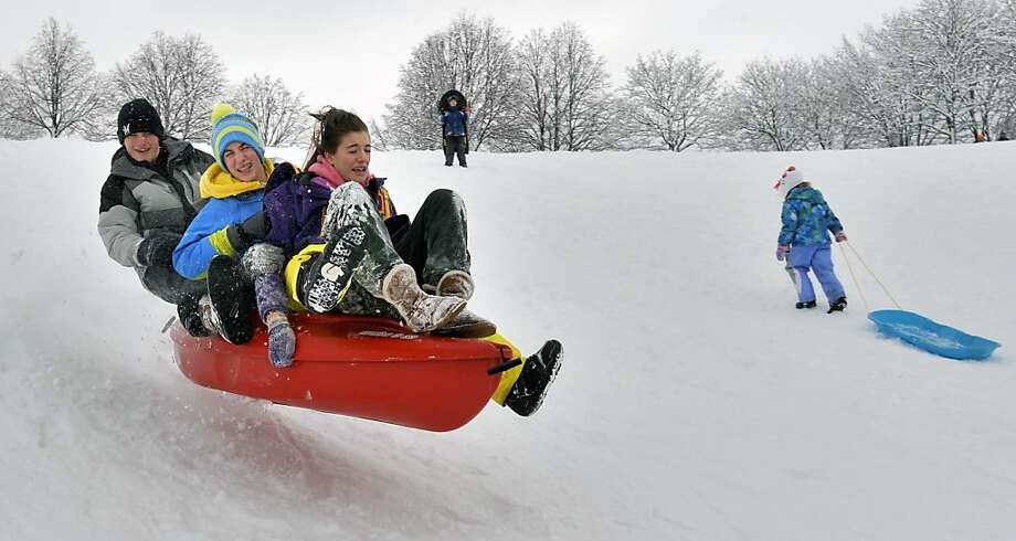 April Malvasio, Nick Sprasky, Jordan Ganther (hidden) and Reid Heinart go airborne in a kayak as they careen down the sledding hill at Lockwood Park on a snow day on Friday, February 8, 2013 in Racine, Wis.  Photo: Scott Anderson, Associated Press