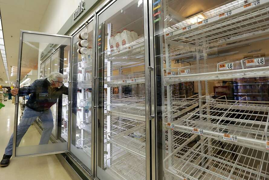 Jack Percoco of Cambridge, Mass. reaches into depleted shelves for milk at a supermarket in Somervil
