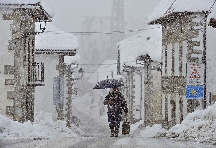 A man shelters by the snow under an umbrella walking on the road, in El Espinal, northern Spain, Friday Feb. 8, 2013. A cold spell has reached northern Spain with temperatures plummeting far below zero.  Photo: Alvaro Barrientos, Associated Press