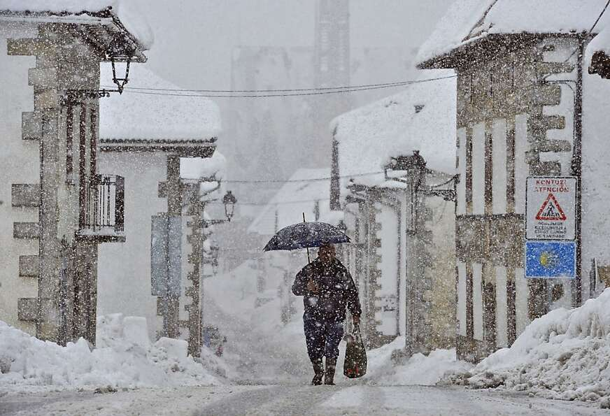 A man shelters by the snow under an umbrella walking on the road, in El Espinal, northern Spain, Fri