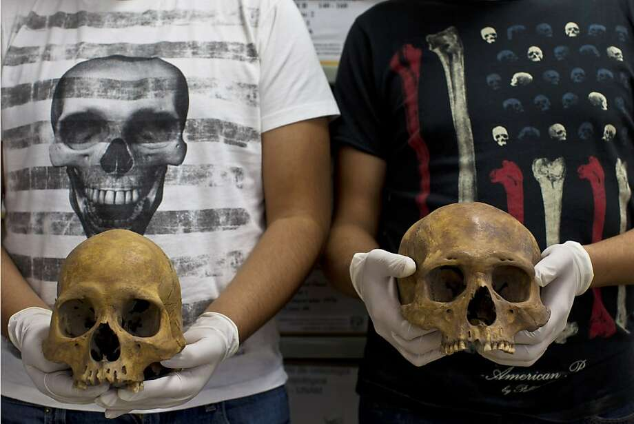Students pose holding skulls from the recently discovered Xaloctan site at the National Institute of Anthropological Studies at Mexico's National Autonomous University in Mexico City, Friday, Feb. 8, 2013. Archaeologists say they have turned up about 150 skulls of human sacrifice victims at a field in Xaloctan, central Mexico near the Teotihuacan pyramids. Experts are puzzled by the unexpected find of such a large number of skulls at what appears to have been a small, unremarkable shrine. The heads were carefully deposited in rows or in small mounds, mostly facing east toward the rising sun, sometime between 660 and 860 A.D.  Photo: Dario Lopez-Mills, Associated Press