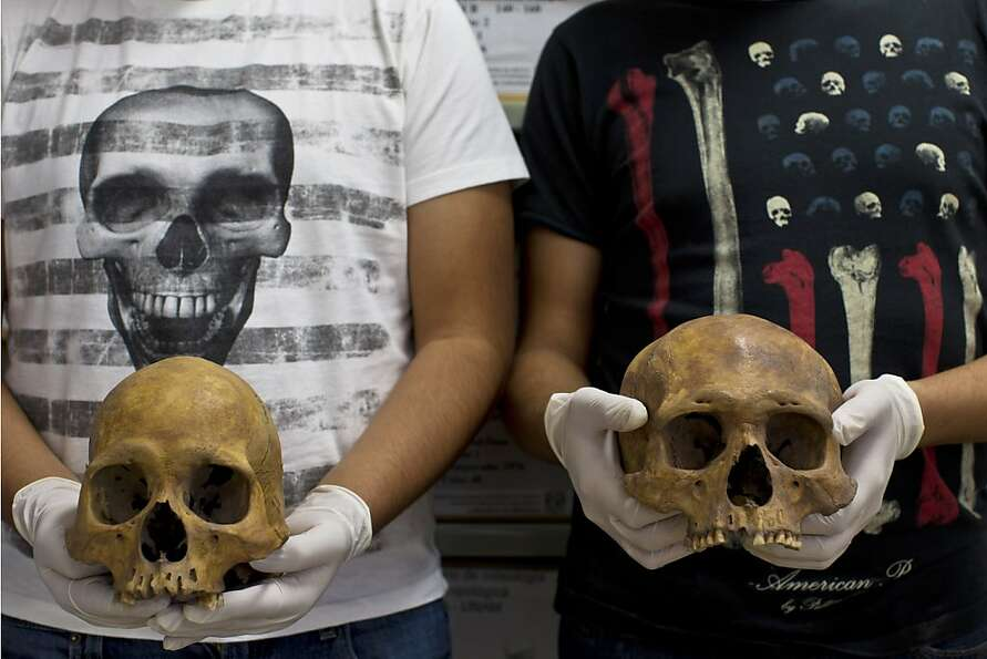 Students pose holding skulls from the recently discovered Xaloctan site at the National Institute of