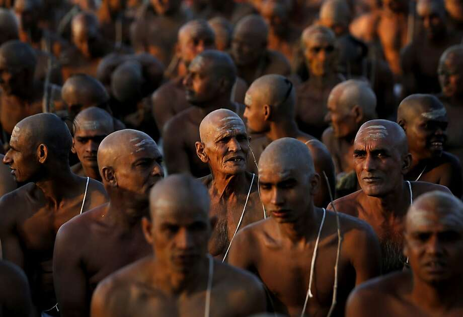 "Hindu holy men of the Awahan Akhara sit with their heads freshly shaven as they participate in initiation ritual that is believed to rid them of all ties in this life and dedicate themselves to serving God as a ""Nagas"" or naked holy men, at Sangam, the confluence of the Ganges and Yamuna River during the Maha Kumbh festival in Allahabad, India , Friday, Feb. 8, 2013. The significance of nakedness is that they will not have any worldly ties to material belongings, even something as simple as clothes. This ritual that transforms selected holy men to Naga can only be done at the Kumbh festival. Photo: Kevin Frayer, Associated Press"