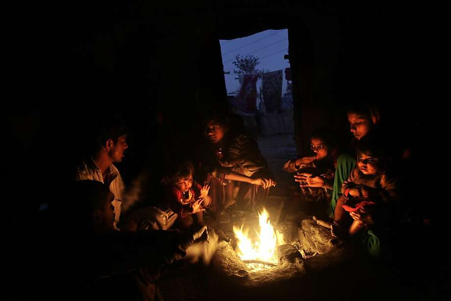 A Pakistani family, which was displaced by 2010 floods from a village in Pakistan's Sindh province, gather around a fire they lit inside their makeshift tent to warm themselves from the night cold, in a slum on the outskirts of Islamabad, Pakistan, Friday, Feb. 8, 2013.  Photo: Muhammed Muheisen, Associated Press