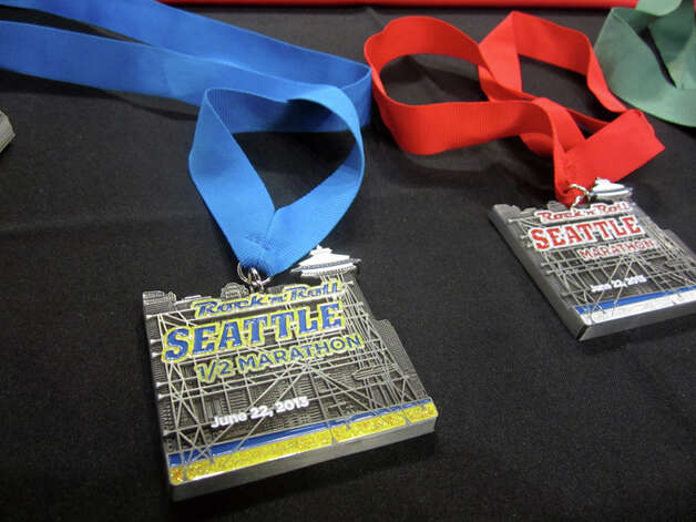 Organizers showed the finisher's medals for the Rock 'n' Roll Seattle Marathon and Half Marathon Friday night at Road Runner Sports in Green Lake. Photo: Casey McNerthney/seattlepi.com