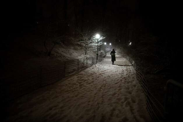 A pedestrian walks along a snowy path in Central Park, Friday, Feb. 8, 2013, in New York. Snow began falling across the Northeast on Friday, ushering in what was predicted to be a huge, possibly historic blizzard and sending residents scurrying to stock up on food and gas up their cars. (AP Photo/John Minchillo) Photo: John Minchillo, Associated Press / FR170537 AP