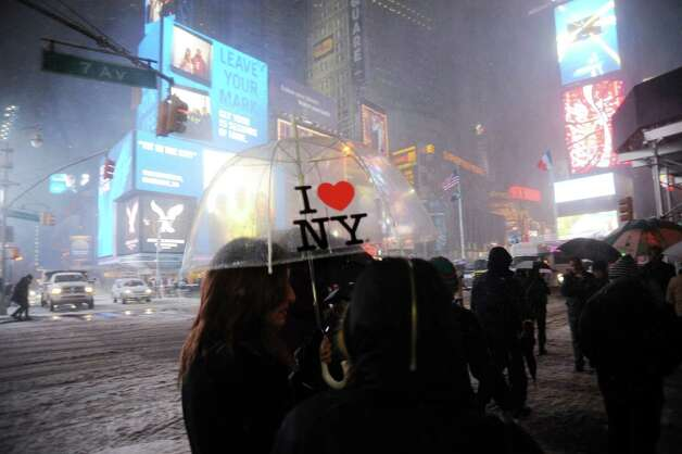 "People walk in the snow in Times Square in New York on February 8, 2013 during a storm affecting the northeast US. The storm was forecast to bring the heaviest snow to the densely-populated northeast corridor so far this winter, threatening power and transport links for tens of millions of people and the major cities of Boston and New York. New York and other regional airports saw more than 4,500 cancellations ahead of what the National Weather Service called ""a major winter storm with blizzard conditions"" along most of the region's coastline. AFP PHOTO / MEHDI TAAMALLAHMEHDI TAAMALLAH/AFP/Getty Images Photo: MEHDI TAAMALLAH, AFP/Getty Images / AFP"