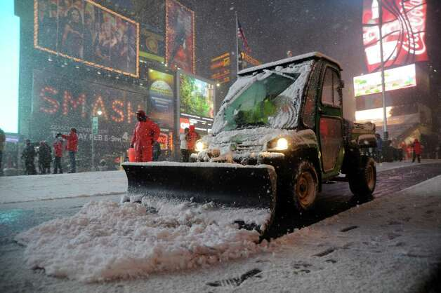 "Workers shovel snow in Times Square in New York on February 8, 2013 during a storm affecting the northeast US. The storm was forecast to bring the heaviest snow to the densely-populated northeast corridor so far this winter, threatening power and transport links for tens of millions of people and the major cities of Boston and New York. New York and other regional airports saw more than 4,500 cancellations ahead of what the National Weather Service called ""a major winter storm with blizzard conditions"" along most of the region's coastline. AFP PHOTO / MEHDI TAAMALLAHMEHDI TAAMALLAH/AFP/Getty Images Photo: MEHDI TAAMALLAH, AFP/Getty Images / AFP"