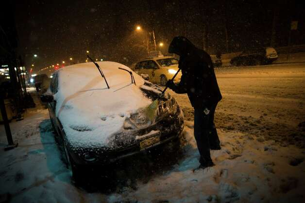 A motorist clears snow from his car on 59th Street, Friday, Feb. 8, 2013, in New York. Snow began falling across the Northeast on Friday, ushering in what was predicted to be a huge, possibly historic blizzard and sending residents scurrying to stock up on food and gas up their cars. (AP Photo/John Minchillo) Photo: John Minchillo, Associated Press / FR170537 AP